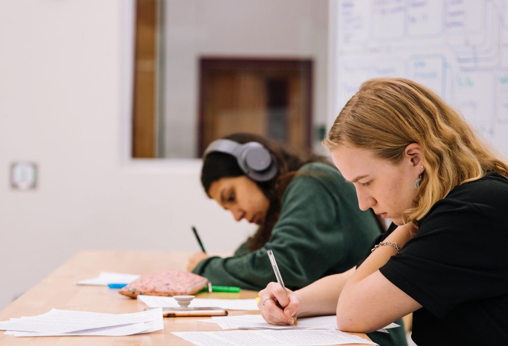 A male and female student doing their work in a school classroom.