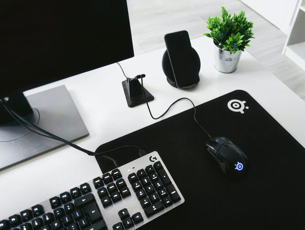 Computer, mouse, keyboard and phone on top of a sleek white desk.