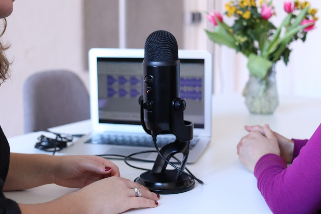 Two women recording a podcast together at a table with their laptop.