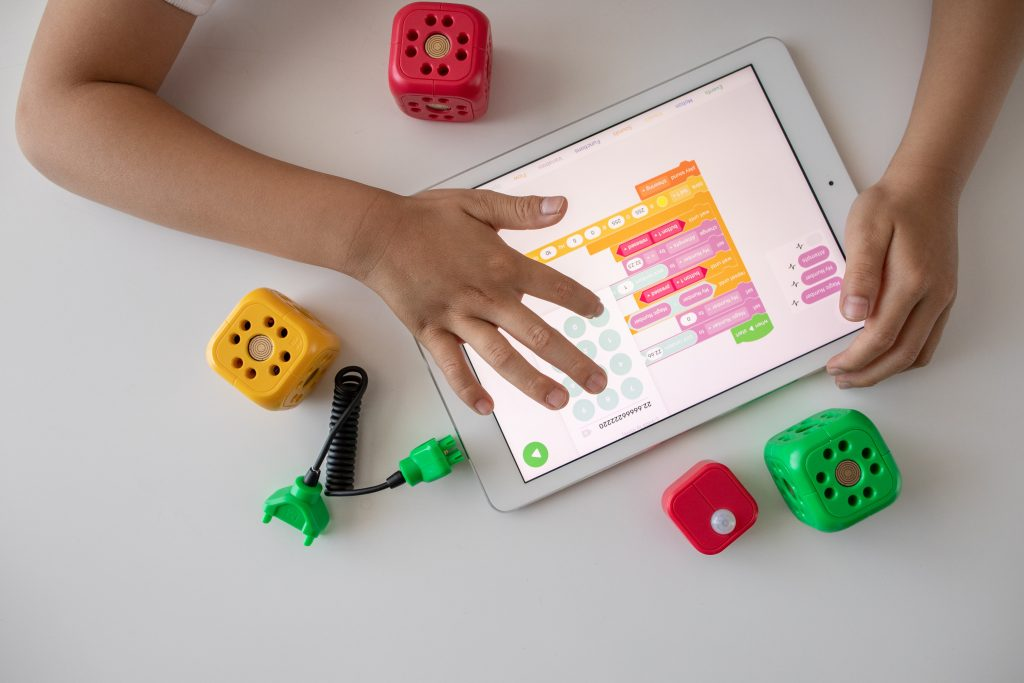 Young child playing on an iPad with toys around them.